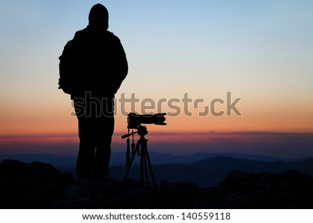 Silhouette of a photographer with his camera on a hilltop - stock photo