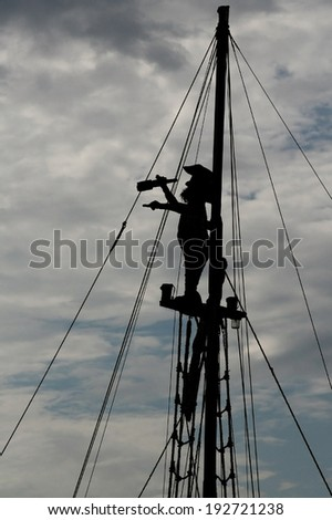 silhouette of a pirate on the match looking through spyglass  ( not an actual pirate , imitation)  - stock photo