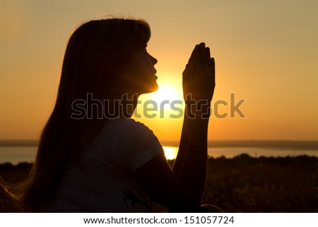 silhouette of a praying girl at sunset - stock photo