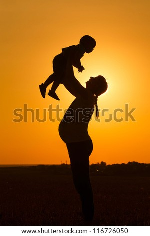 Silhouette of a pregnant woman raising her son at sunset