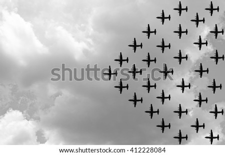 Silhouette of a propeller military airplane in an attack formation against a gloomy cloudy sky. Processed in monochrome. - stock photo