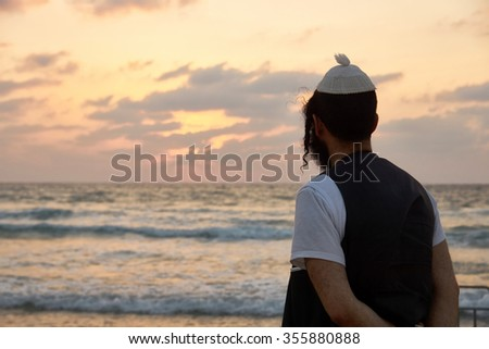 Silhouette of a religious Jewish man contemplating and thinking by the ocean Tel Aviv Israel                              - stock photo
