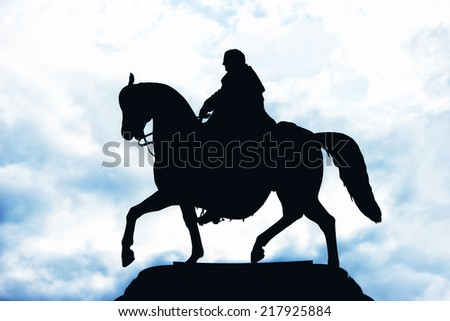 Silhouette of a rider on a horse on sky background