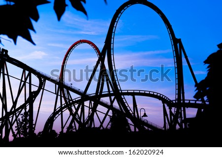 silhouette of a roller coaster at a blue sunset during a fun fair at entertainment thematic park - stock photo