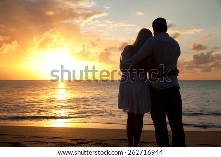 Silhouette of a romantic couple on a beach at sunset