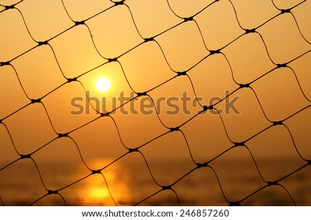 Silhouette of a romantic sunset evening on a calm peaceful beach on one of the finest beaches in India,The Cherai Beach,kochi,Kerala as seen through the fishing nets in a restaurant/hotel - stock photo