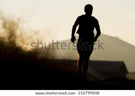 Silhouette of a runner during the sunrise - stock photo