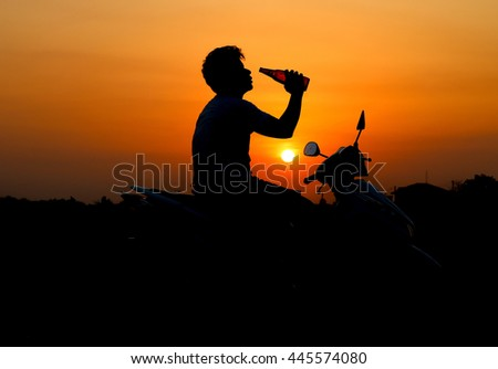 Silhouette of a sad man drinking beer bottle at sunset background
