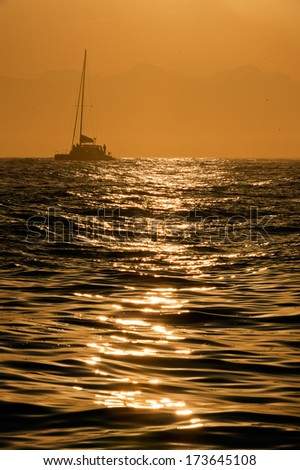 Silhouette of a sailboat on Atlantic ocean at sunrise - stock photo