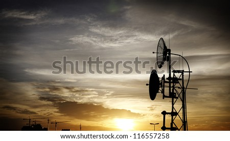 Silhouette of a satellite dish and radio antennae on a telecommunication tower against a fiery sunset sky.