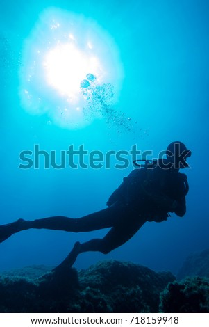 Silhouette of a scuba diver in the deep blue