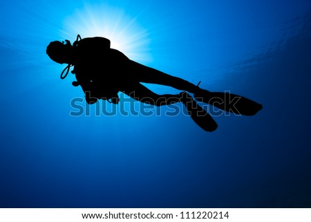 Silhouette of a SCUBA Diver with a sunburst - stock photo