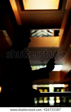 silhouette of a security guard with a portable wireless transceiver in his hand checking the area inside of a blurry building