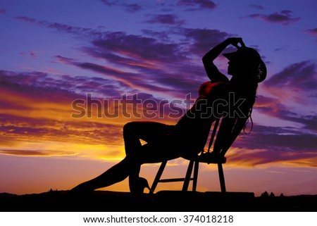 Silhouette of a sexy cowgirl leaning back in a chair. - stock photo