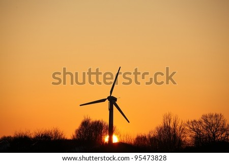 Silhouette of a single windmill at sunset