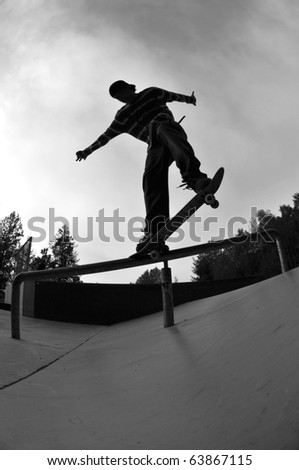 Silhouette of a skateboarder doing a trick - stock photo