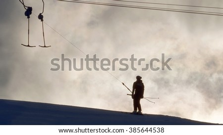 Silhouette of a ski lift and and lonely skier in evening light - stock photo