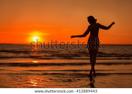 silhouette of a slender girl standing on the beach at sunset