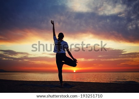 silhouette of a slender woman doing yoga on the sea with a beautiful sunrise