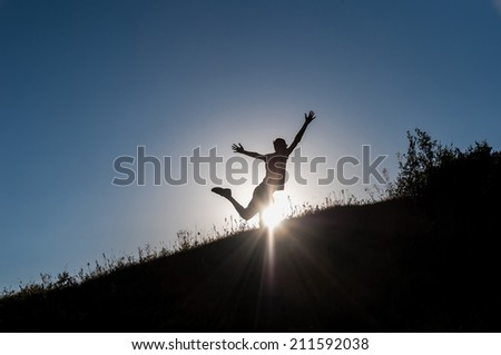 Silhouette of a slender young man making figures in the rays of the sun on the hillside. He's young, fun, free and happy. - stock photo