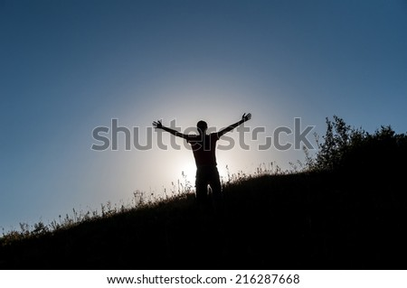 Silhouette of a slender young man making figures in the rays of the sun on the hillside. He's young, fun, free and happy.