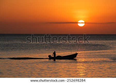 Silhouette of a small boat against a golden sunset, Zanzibar island