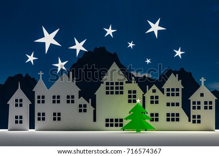 Silhouette of a small village at winter time in the night. With stars in the sky