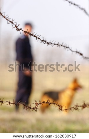 Silhouette of a soldier and wolf dog behind a barbed wire fence