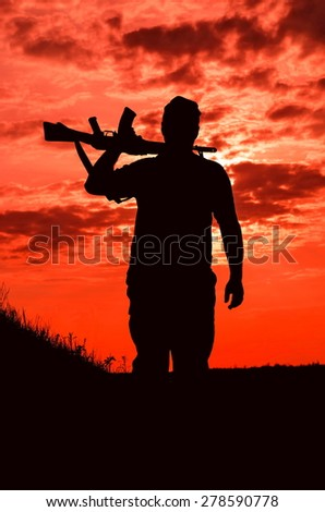 silhouette of a soldier with a gun on a background of the fiery sky - stock photo