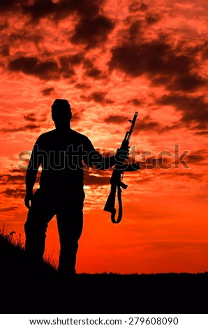 silhouette of a soldier with a gun on a background of the fiery sky