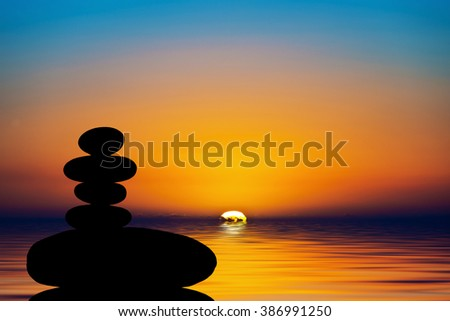 Silhouette of a stack of stones in the sunset - stock photo