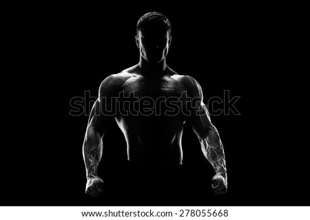 Silhouette of a strong bodybuilder. Confident young fitness man with strong hands and clenched fists. Black and white photo. Dramatic light.