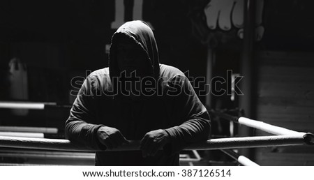 Silhouette of a strong fighter. Confident young fitness man with strong hands and clenched fists. Dramatic light. - stock photo