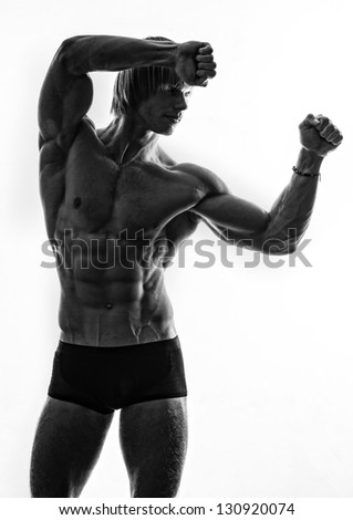 Silhouette of a strong male model - stock photo