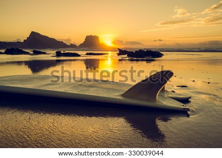 Silhouette of a surfboard at the beach with reflection  - stock photo