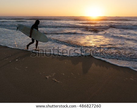 Silhouette of a surfer in front of the sea with golden waves  at sunset.