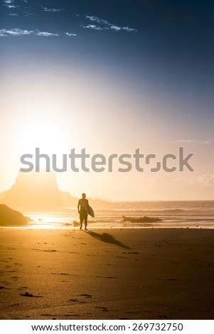 Silhouette of a surfer man at the beach with his surfboard - stock photo