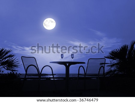 Silhouette of a table with wine glasses on a moon night