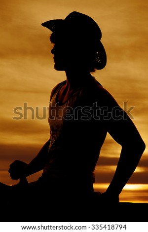 Silhouette of a teen cowboy sitting in the saddle on his horse. - stock photo