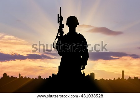 Silhouette of a terrorist with a weapon against a background of the urban landscape at sunset. The concept of terrorism and war