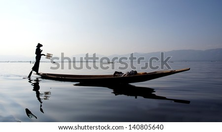silhouette of a traditional fishers boat on the Inle lake in Myanmar  - stock photo
