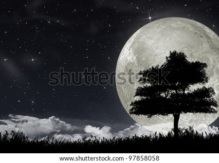 Silhouette of a tree against the big moon and the star night sky. - stock photo