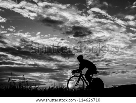 Silhouette of a triathlete in cycling - stock photo