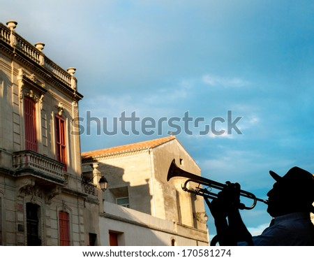 Silhouette of a trumpeter on Arles street, France - stock photo