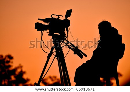 Silhouette of a TV cameraman against a sunset - stock photo