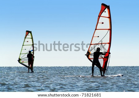 Silhouette of a two windsurfers on the sea surface