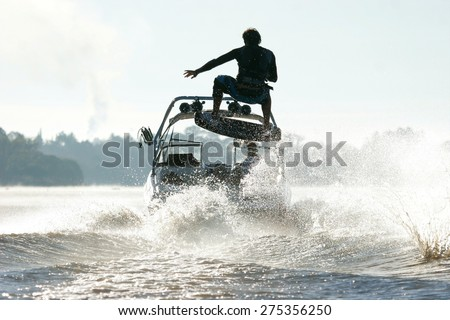 Silhouette of a wake skater as he launches off the wake behind a boat. - stock photo