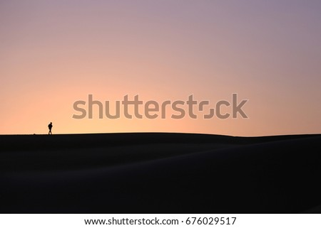 Silhouette of a walking man in desert with the background of golden sunset