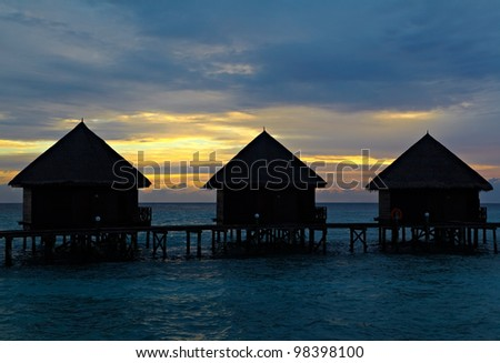 Silhouette of a water villa at sunset in the sea - stock photo
