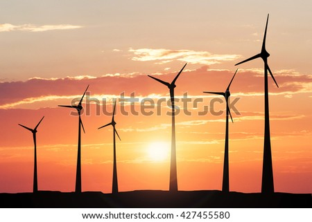 Silhouette Of A Windmill At Sunset Generating Electricity